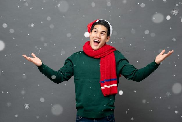 Взволнованный азиатский человек, носящий рождественскую тему одежды с открытыми ладонями жест