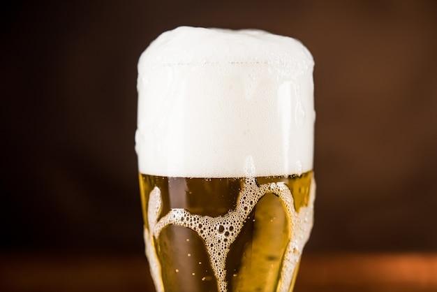 オーバーフローの泡状泡が付いたテーブルの上のグラスに冷たいビール