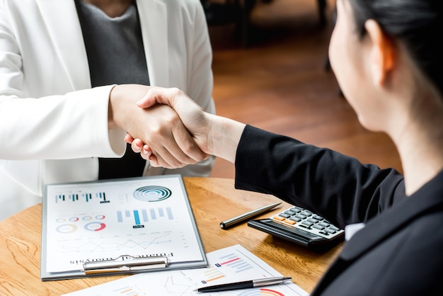 オフィスラウンジで握手をする実業家リーダー