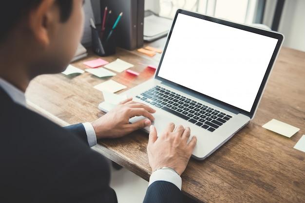 彼の机で空の白い画面を持つラップトップコンピューターに取り組んでいるビジネスマン