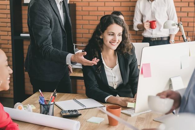 コンピューターの前に同僚と働く若いロシアビジネス女性