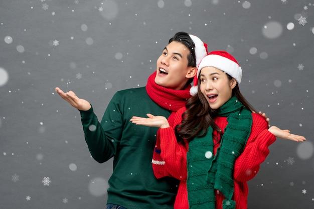 開いた手のひらジェスチャーでクリスマステーマの服を着て興奮したアジアカップル