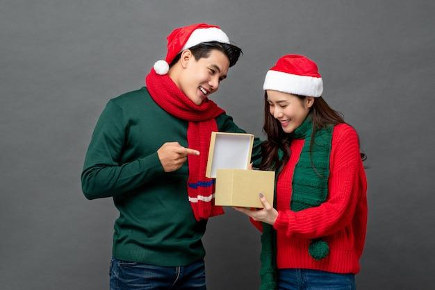 Счастливая удивленная азиатская женщина раскрывая подарочную коробку рождества подаренную ее парнем