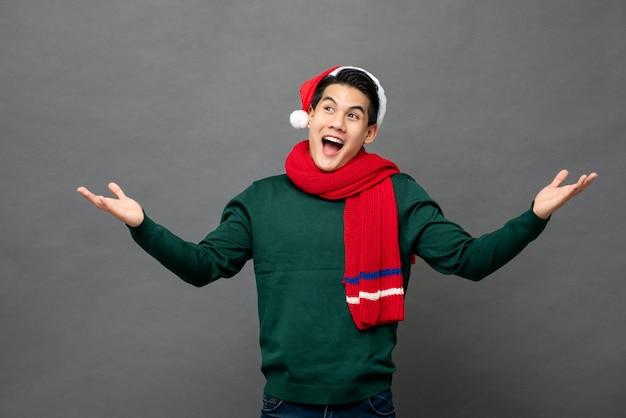 開いた手のひらジェスチャーでクリスマステーマの服を着て面白がってアジア人