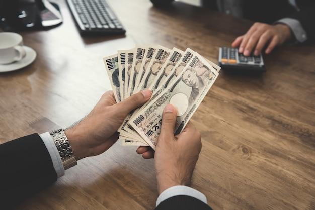 オフィスで日本円のお金を数える実業家