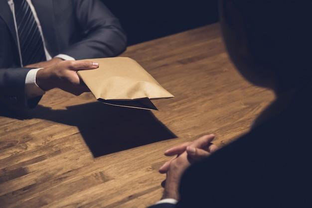 Мужчина дает взятку в коричневом конверте другому бизнесмену