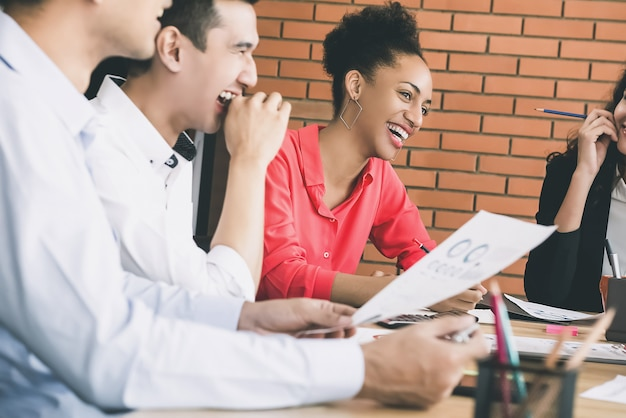 笑って、会議で楽しんでいる多民族の千年ビジネス人々