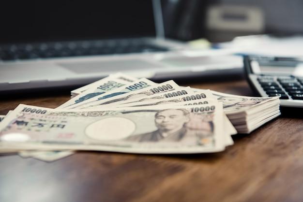 テーブルの上の電卓とノートパソコンと日本円紙幣