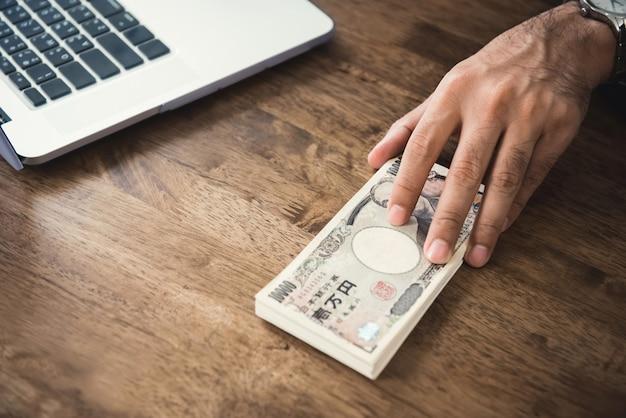 テーブルの上の日本円紙幣のお金を与える実業家