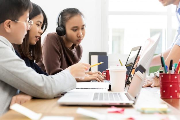 Группа студентов колледжа азии, глядя на портативный компьютер, обсуждая проект