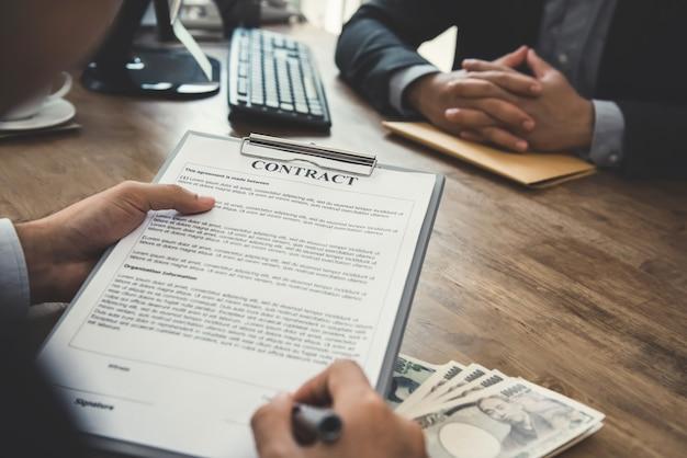 Бизнесмен подписывает договор с деньгами, банкнотами японской иены, на столе