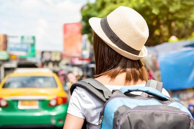 カオサン通りを歩く女性観光バックパッカーの背面図、バンコクでの休日に一人旅