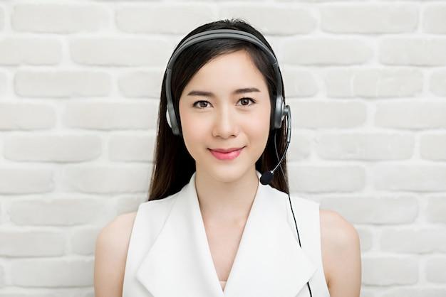 Красивая азиатская коммерсантка нося шлемофон микрофона как агент обслуживания клиента телемаркетинга