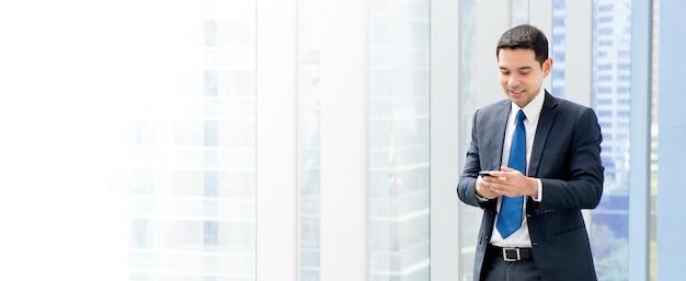 アジア系のビジネスマンに立って、オフィスビルの廊下でスマートフォンを使用して