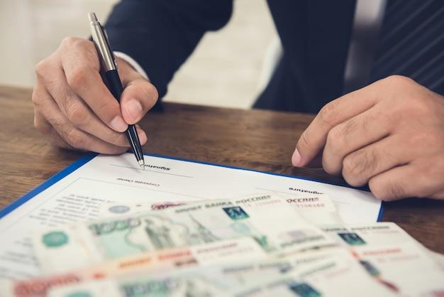 Бизнесмен подписывает договор контрактной бумаги с деньгами, российские рублевые купюры, на столе
