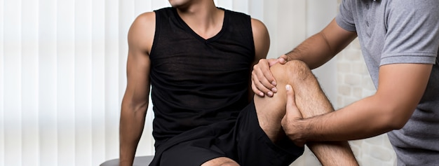 Терапевт лечит травмированное колено спортсмена мужского пола пациента в клинике