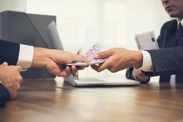 作業机の上の彼のパートナーにお金、ユーロ紙幣を与える実業家