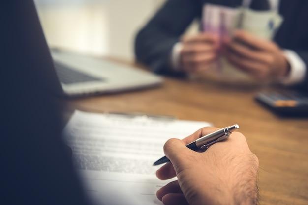 Бизнесмен рассматривает и подписывает договорный договор со своим партнером