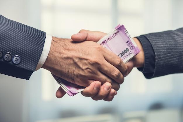 Бизнесмены делают рукопожатие с деньгами, валютой индийской рупии, в руках