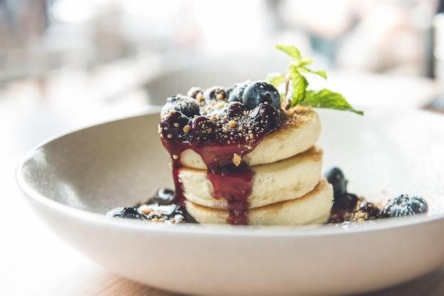 Красивая аппетитная стопка пушистых блинов со свежей черникой, сиропом и бисквитом