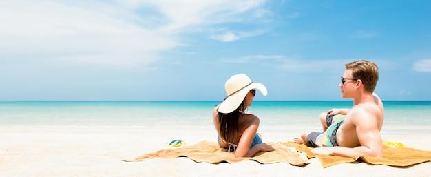 Пара лежит на белом песчаном пляже, отдыхая и принимая солнечные ванны в летние каникулы