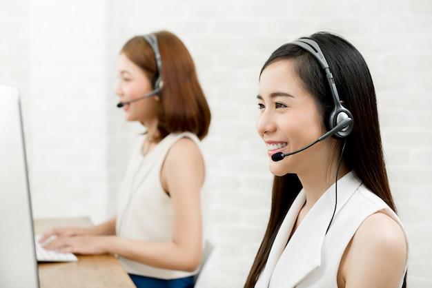 Команда агента обслуживания клиента телемаркетинга азиатской женщины работая в центре телефонного обслуживания