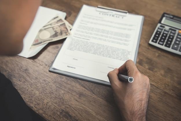 Рука, держащая ручку, подписывающая контракт с деньгами, валютой японской иены, на столе
