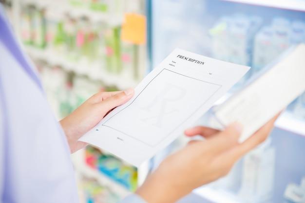 Аптекарь женщины держа рецепт проверяя медицину в аптеке