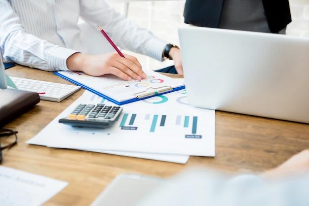 財務グラフドキュメント、ノートブックコンピューター、電卓の作業テーブルで実業家