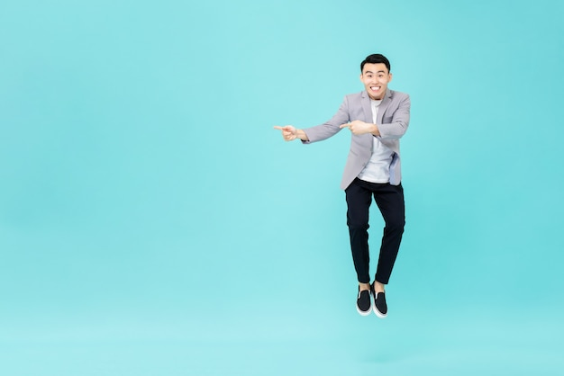 ジャンプして手をコピースペースに手を指している若い笑顔のアジア人