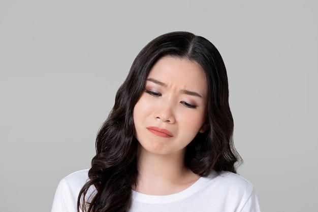 悲しいことに泣いている不幸な若いアジア女性