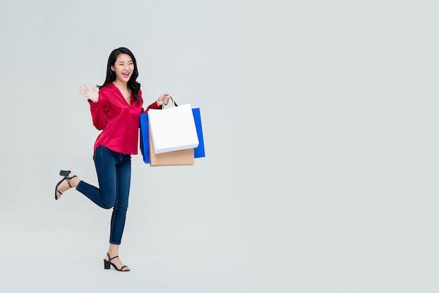 Улыбающаяся возбужденная молодая азиатская девушка с хозяйственными сумками