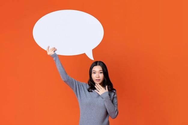 Азиатская девушка в серой футболке держит пустой речи пузырь