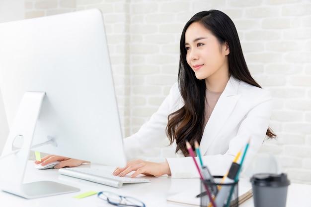 Красивая работница, используя компьютер в офисе