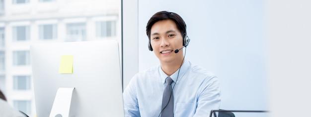 Агент телемаркетинга азиатского человека в офисе центра телефонного обслуживания