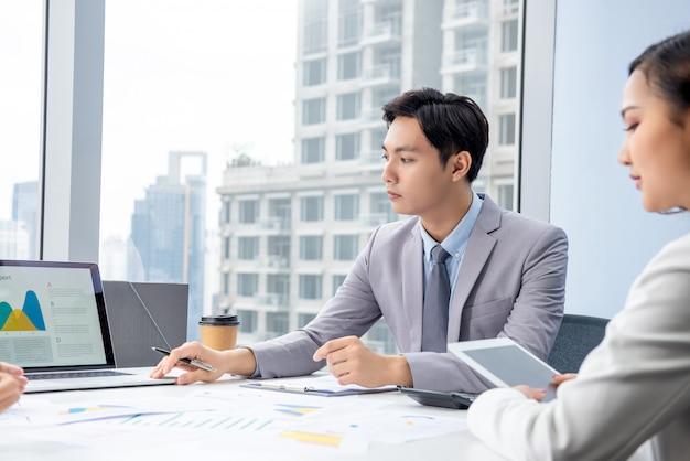 Азиатский бизнесмен представляя диаграмму данных на встрече