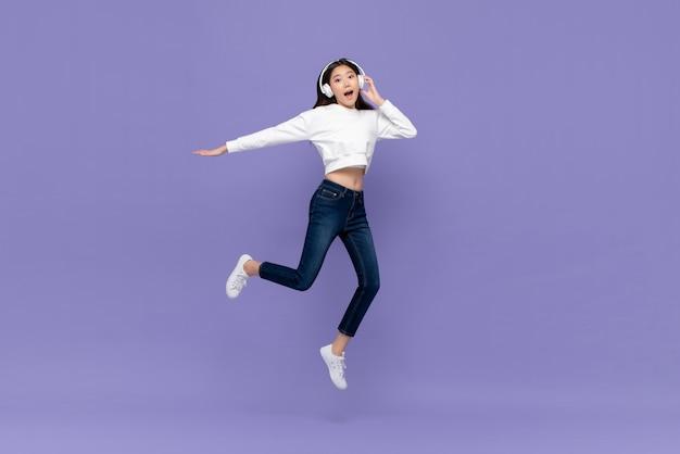 アジアの女性のジャンプとヘッドフォンで音楽を聴く