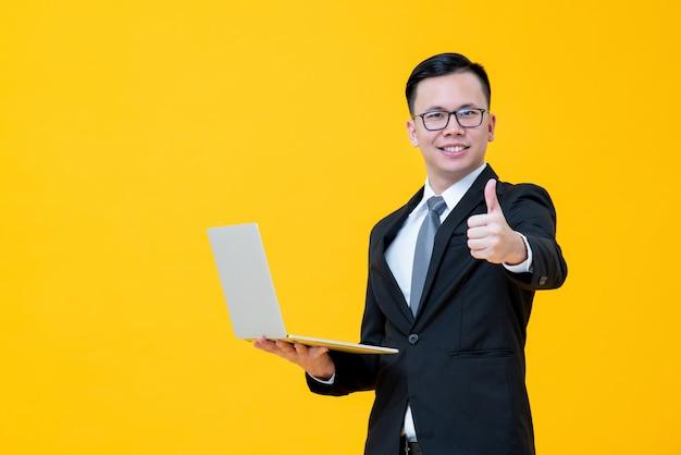 Портативный компьютер азиатского бизнесмена нося и давать большие пальцы руки вверх