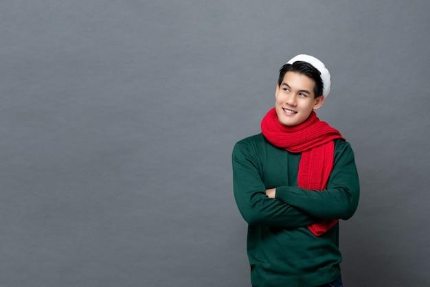 Улыбаясь азиатских человек в рождественской одежде, глядя вверх со скрещенными руками