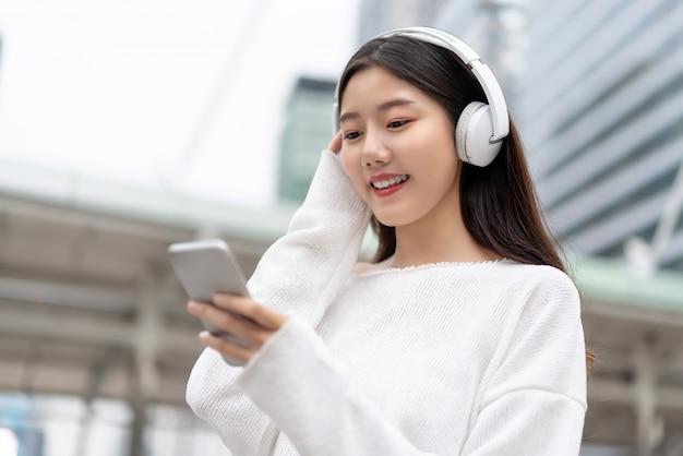 Наушники азиатской девушки нося слушая к потоковой музыке от умного телефона