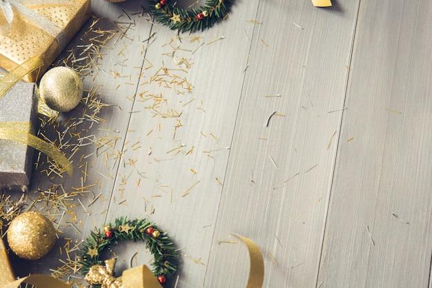 コピースペースとウッドの背景上のアイテムを飾る光沢のあるクリスマス