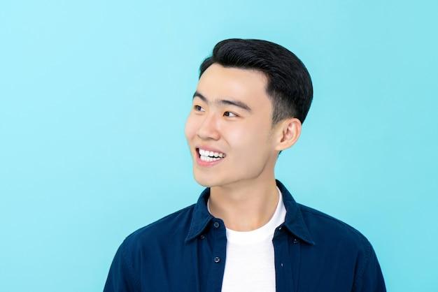 Счастливый молодой азиатский человек улыбается и смотрит в сторону