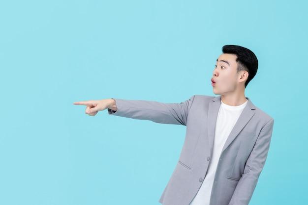 Молодой азиатский бизнесмен смотря удивленный пока указывающ рука для того чтобы скопировать космос