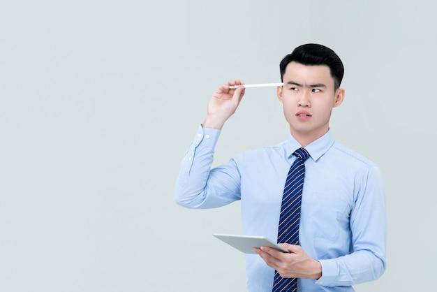 コピースペースの横にある頭にスタイラスを保持している思慮深いアジア専門の若者