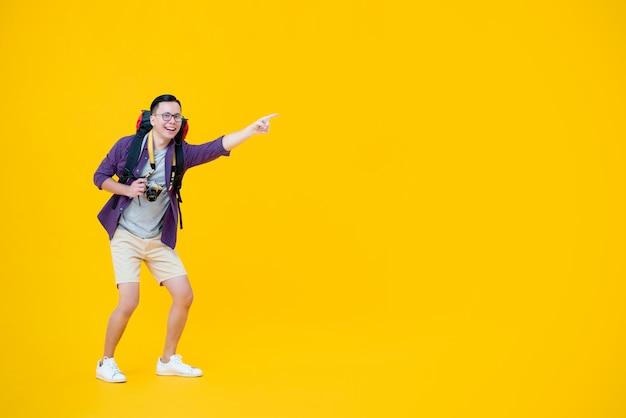若い幸せなアジア男性バックパッカー笑顔とカメラを押しながら指して