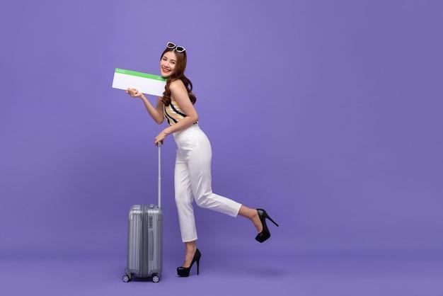 Молодой счастливый азиатский турист женщины с багажом и билетом на самолет