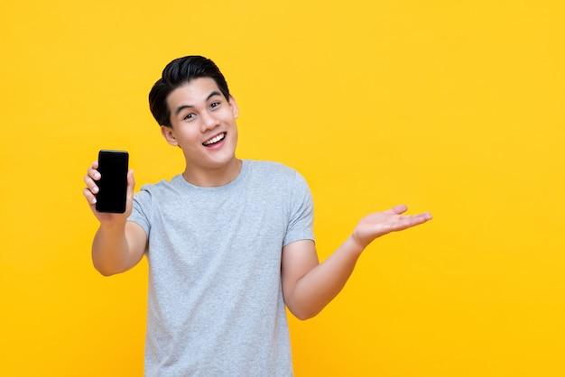 別の手を開いて携帯電話を示す幸せな笑みを浮かべて若いアジア人