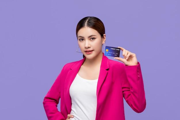 Красивая азиатская женщина в красочном розовом костюме показывая кредитную карточку в руке