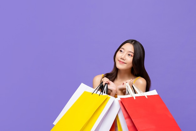 Довольно азиатская женщина держа красочные покупки назад думая и смотря прочь