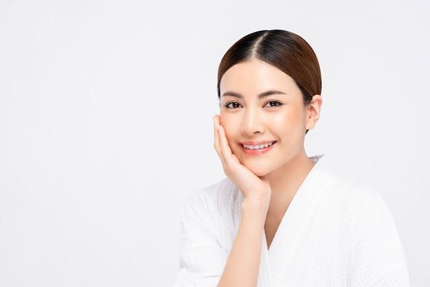 アジアの女性の顔に触れる手で明るい肌の美しさのショット